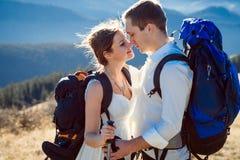 Härliga tourustbrölloppar som kysser i bergen bröllopsresa Royaltyfri Fotografi