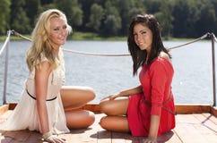 Härliga unga kvinnor på en lakepontoon Royaltyfria Bilder
