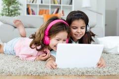 Härliga unga systrar som lyssnar till musik med digital minnestavla a Arkivfoton