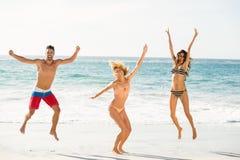 Härliga upphetsade vänner som hoppar på stranden Arkivfoton