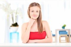 Härligt flickasammanträde på en tabell inomhus Royaltyfri Foto