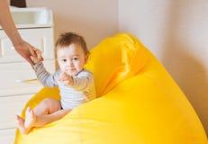 Härligt förtjusande skratta behandla som ett barn den begynnande framsidan för pojken Att le barnet sitter på en stol Royaltyfri Bild