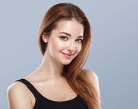 Härligt kvinnaframsidaslut upp ung studio för stående på blått Royaltyfri Foto