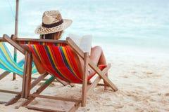 Härligt kvinnasammanträde på strandläsning en boka Arkivbild