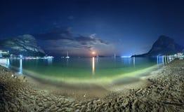 Härligt nattlandskap på kusten med gul sand, fullmånen, berg och den mån- banan moonrise Semestrar på stranden Royaltyfri Bild