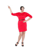 Härligt plus formatkvinna i röd klänningvisning på något Royaltyfri Foto