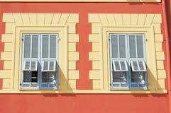 Härligt rött stuckaturhus med två blåa traditionella franska slutarefönster i Nice, Frankrike Royaltyfri Foto