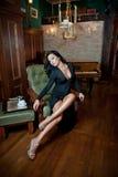 Härligt sexigt flickasammanträde på stol och att koppla av Stående av brunettkvinnan med långa ben som poserar att utmana sinnlig Royaltyfria Bilder