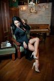 Härligt sexigt flickasammanträde på stol och att koppla av Stående av brunettkvinnan med långa ben som poserar att utmana sinnlig Arkivfoton
