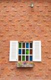 Härligt wood fönster med mång- färgexponeringsglas och tegelstenväggen Royaltyfria Bilder