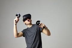 Hörlurar med mikrofon för virtuell verklighet för television för kvinna hållande ögonen på bärande Arkivfoto
