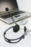 hörlurar med mikrofonbärbar dator Arkivbild