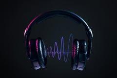 Hörlurar och diskovågor som isoleras på svart bakgrund Arkivbild