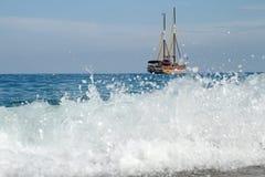 Hrough在海岛上的海浪有美丽的船的 免版税库存照片