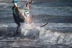 Hrough de golven Meisje het windsurfing bij de Atlantische Oceaan/Gr Medano, Tenerife, Spanje royalty-vrije stock foto's
