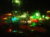 Hrough the rain. through the glass. look at the illuminated city Royalty Free Stock Image