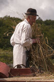 HRUSOV, ESLOVAQUIA - 16 DE AGOSTO: El viejo granjero en traje tradicional llena la trilladora durante el festival Hontianska Para Imágenes de archivo libres de regalías
