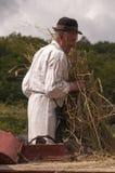 HRUSOV, SLOWAKEI - 16. AUGUST: Alter Landwirt im traditionellen Kostüm füllt die Dreschmaschine während des Folklorefestivals Hon Lizenzfreie Stockbilder