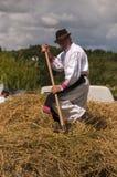 HRUSOV, SLOWAKEI - 16. AUGUST: Alter Landwirt im traditionellen Kostümsammelnstroh während des Folklorefestivals Hontianska Parad Stockfotografie