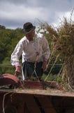 HRUSOV, SLOWAKIJE - AUGUSTUS 16: De oude landbouwer in traditioneel kostuum vult de dorser tijdens folklorefestival Hontianska Pa stock foto's