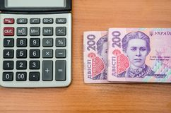 200 hryvnia and a calculator on a wooden table. Close-up. royalty free stock photos
