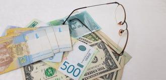 Hryvnia dolary blisko eyeglasses na bielu stole i dynars fotografia royalty free