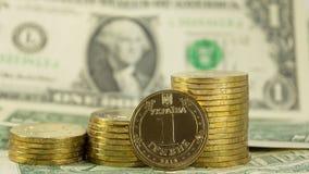 Hryvnia ucraniano de la moneda (grivna) en el fondo de las cuentas de los E.E.U.U. de 1 dólar (1 USD) Fotos de archivo libres de regalías