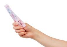 Hryvnia ukrainien de l'argent 200 dans la main femelle sur le blanc Photos stock
