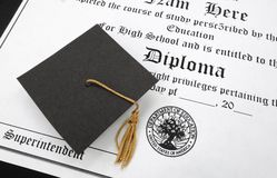 Hs diploma. A mini graduation cap on a high school diploma Royalty Free Stock Photos
