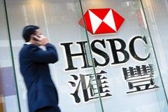 HSBC Bank Sign in Hong Kong. Hong Kong, Hong Kong SAR -November 17, 2014: Motion blured business man passing by an HSBC Bank sign in Hong Kong. HSBC Holdings plc stock images