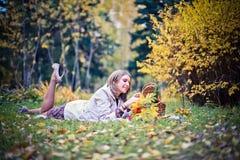 Höstkvinnan som är lycklig i nedgång, parkerar lägger på korgen som har gyckel som ler i härlig färgrik skoglövverk Arkivfoton