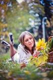 Höstkvinnan som är lycklig i nedgång, parkerar lägger på korgen som har gyckel som ler i härlig färgrik skoglövverk Royaltyfria Bilder