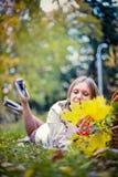 Höstkvinnan som är lycklig i nedgång, parkerar lägger på korgen som har gyckel som ler i härlig färgrik skoglövverk Royaltyfri Fotografi