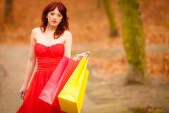 Höstshopparekvinnan med försäljning hänger löst utomhus- parkerar in Royaltyfri Foto