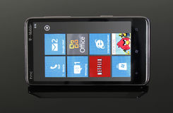 HTC HD7 running Windows Phone 7. Picture an HTC HD7 running Windows Phone 7 on a reflective, smoked glass table Stock Image