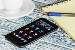 HTC Mobile Phone with Android applications on the desktop Royalty Free Stock Photo