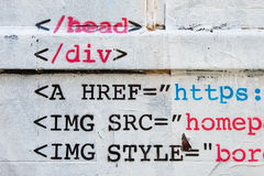 HTML stencil graffiti on brick wall. Stencil of HTML code on white wall Royalty Free Stock Photo
