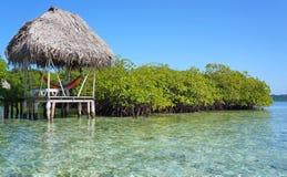 Hütte mit Hängematte über dem Meer Stockbilder
