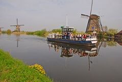 Tourists enjoy local boat tour on a Dutch river stream at Kinderdijk with view of Windmills, Netherlands