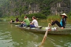 Tourists enjoy the ride & boat rower looking at the camera while rowing using feet through cliffs at Tam Coc, Vietnam