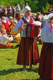 Celebrating anniversary in Turaida, Latvia with young girls playing musical instrument and performance in traditional costumes