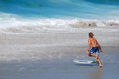 Huésped de la leche desnatada prreparing para montar una onda de la rotura de la orilla en la playa en Laguna Beach, California d Foto de archivo