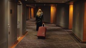 Huésped del hotel con la caja de la carretilla que camina al cuarto metrajes