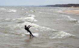 huésped y persona que practica surf de la cometa en agua fría  Fotografía de archivo libre de regalías