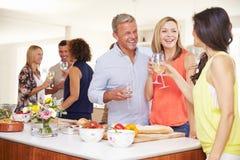 Huéspedes maduras que son dadas la bienvenida en el partido de cena por los amigos Fotos de archivo libres de regalías