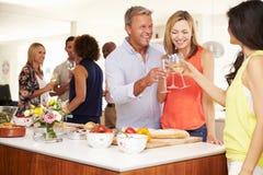 Huéspedes maduras que son dadas la bienvenida en el partido de cena por los amigos Fotografía de archivo libre de regalías