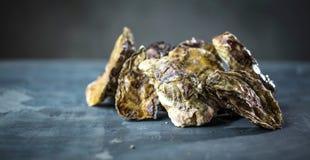 Huîtres crues fraîches dans des mains de l'homme sur le bakground foncé images stock
