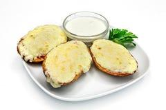 Huîtres cuites au four avec du fromage et la sauce d'un plat sur un fond blanc Photos stock
