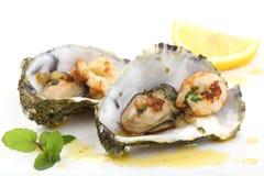 Huîtres et crevettes roses frites dans une coquille d'isolement sur le blanc Photos stock