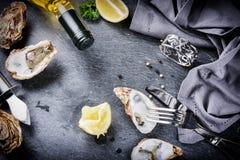 Huîtres fraîches avec du vin blanc et le citron sur le fond en pierre Photographie stock libre de droits